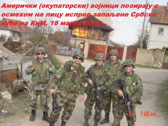 US soldiers from KFOR force smiling while in their background Serbian house goes up in flames KOSOVO 2004